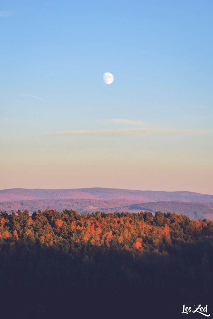 La lune se révèle au dessus de la forêt flamboyante de la Margeride